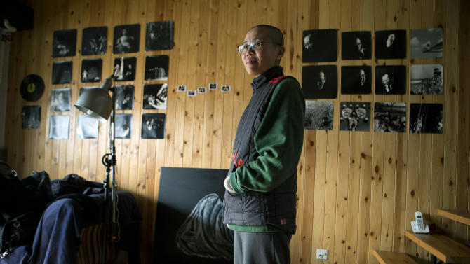 Liu Xia, wife of 2010 Nobel Peace Prize winner Liu Xiaobo, stands in her home where she has been held under house arrest for more than two years in Beijing, China, on Thursday, Dec. 6, 2012. Liu trembled uncontrollably and cried Thursday as she described how her confinement under house arrest has been absurd and emotionally draining in the two years since her jailed activist husband was named a Nobel Peace laureate.  (AP Photo/Ng Han Guan)