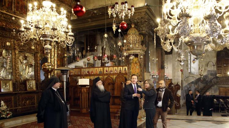 British Prime Minister David Cameron talks to officials as he visits the Church of the Nativity in Bethlehem