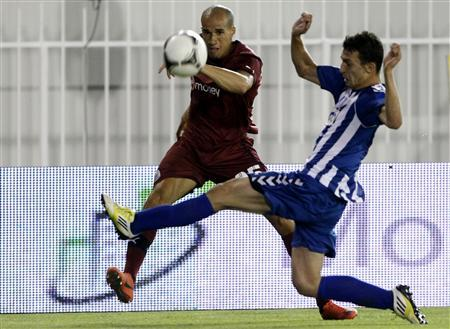 Atromitos' Konstantinos Giannoulis challenges Newcastle United's Dan Gosling during their Europa League soccer match in Athens