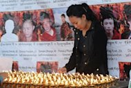 An exile Tibetan woman lights candles at the Tsuglakhang temple in Dharamshala as she mourns the deaths of six Tibetans who self-immolated in protest against Chinese rule