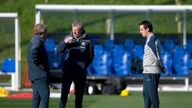 England's manager Roy Hodgson (C) talks with assistant manager Ray Lewington (L) as first team coach Gary Neville looks on during a training session near Burton-on-Trent, central England, on October 8, 2015