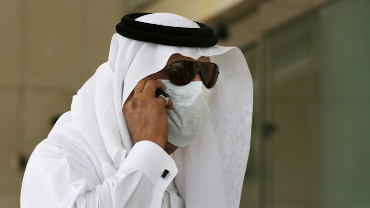 FILE - In this Friday, May 9, 2014 file photo, a Saudi man talks on his phone as he wears a mask outside King Fahd Hospital in Jeddah, Saudi Arabia. Saudi health officials say another five people have died after contracting a potentially fatal Middle Eastern respiratory virus that has sickened hundreds. (AP Photo/Hasan Jamali, File)