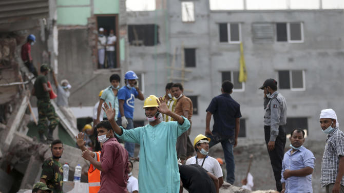 In this photo taken on Saturday April 27, 2013,  volunteer workers at the scene prepare for rescue work. When the Rana Plaza, a garment factory building collapsed, many of the first responders were neighborhood residents, fellow garment workers, relatives of the missing and charity workers, and they repeatedly took some of the most dangerous work.(AP Photo/Wong Maye-E)