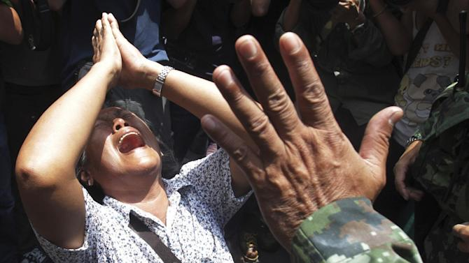 An anti-coup protester cries as she asks a Thai soldier to go away during a demonstration in Bangkok, Thailand, Sunday, May 25, 2014. The top general in Thailand's ruling junta warned people Sunday not to join anti-coup street protests, saying normal democratic principles cannot be applied at the time, as troops fanned out in central Bangkok to prevent rallies. (AP Photo/Sakchai Lalit)
