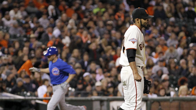 San Francisco Giants relief pitcher Sergio Romo walks back to the mound as Chicago Cubs' Nate Schierholtz rounds the bases after hitting a solo home run during the ninth inning of a baseball game Saturday, July 27, 2013, in San Francisco. (AP Photo/Tony Avelar)