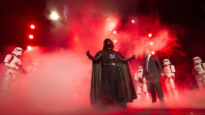 """IMAGE DISTRIBUTED FOR DISNEY CONSUMER PRODUCTS - Disney Consumer Products Executive Vice President Josh Silverman is interrupted by """"The Imperial March"""" led by Darth Vader and 20 Stormtroopers as they take over the stage during a private Disney event at the Licensing Expo, Monday June 17, 2013 at the Mandalay Bay Convention Center in Las Vegas. This surprise grand finale, presented to more than 1,500 licensees, demonstrates a new era of merchandising potential for Disney Consumer Products' robust franchise portfolio, which now includes the Star Wars franchise. (Photo by Eric Jamison/Invision for DisneyConsumer Products/AP Images)"""