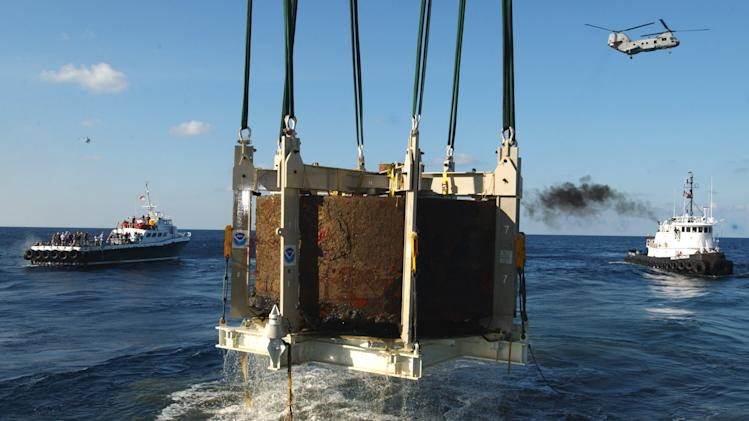 FILE This Monday Aug. 5, 2002 file photo shows the turret of the Civil War ironclad USS Monitor is lifted out of the ocean off the coast of Hatteras NC.  A century and a half after the USS Monitor sank, the interment of remains of two unknown sailors found in the Civil War ironclad's turret is bringing together nearly 100 people from Maine to California who have a distant familial tie to the 16 Union sailors who died when the ship went down. (AP Photo/Steve Helber)