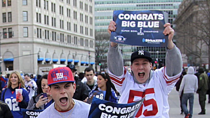Fans cheer as they arrive in lower Manhattan for the start of the New York Giants Super Bowl parade in New York, Tuesday, Feb. 7, 2012.   Eli Manning and the New York Giants are Super Bowl champions again. Just as they did four years ago in Arizona, Tom Coughlin's Giants have defeated Bill Belichick's New England Patriots, this time 21-17 in Indianapolis for their fourth Lombardi Trophy. (AP Photo/Bebeto Matthews)