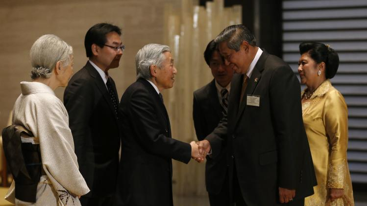 Japan's Emperor Akihito, accompanied by Empress Michiko, shakes hands with Indonesia's President Yudhoyono and his wife Kristiani at the Imperial Palace in Tokyo