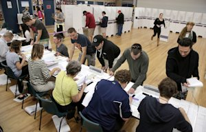 Voters register to receive their ballots at a polling…