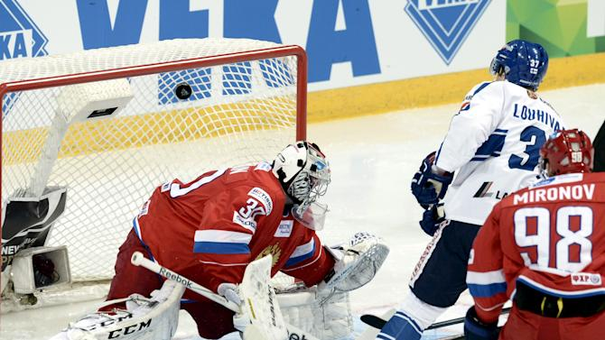 Finland's Ossi Louhivaara (R) scores the game opening goal behind Russia's goalie Konstantin Barulin during Ice Hockey Euro Hockey Tour match Finland vs Russia in Helsinki, Finland