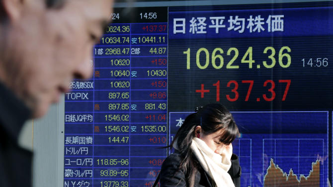 People walk by an electronic stock board of a securities firm in Tokyo, Thursday, Jan. 24, 2013.  Asian stock markets were mostly higher Thursday, supported by Congress averting a U.S. government default and a pickup in China's manufacturing in January. (AP Photo/Koji Sasahara)