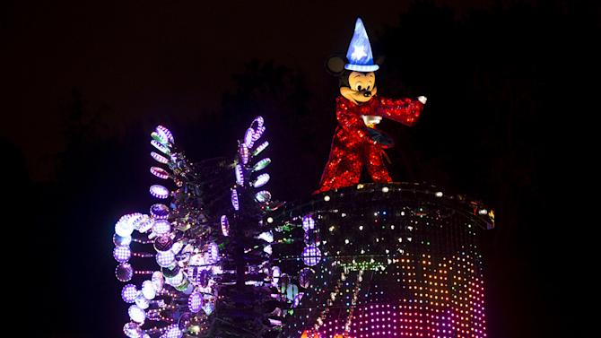 "People watch a float featuring the character of Mickey Mouse during the ""Paint the Night - All-New Electrical Parade"" during Disneyland Diamond Celebration in Anaheim"