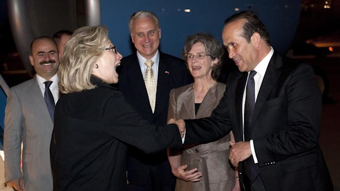 U.S. Secretary of State Hillary Rodham Clinton greets Turkish Ambassador to the U.S., Namik Tan, right, alongside U.S. Ambassador to Turkey Francis Ricciardone, center, and his wife, Marie Ricciardone, after disembarking from her airplane upon arrival in Istanbul, Turkey, Friday, July 15, 2011, for two days of meetings on Libya. (AP Photo/Saul Loeb, Pool)