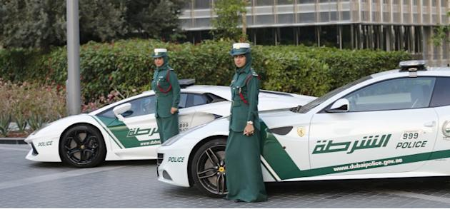 Emirati female police officers pose in front of Lamborghini (L) and Ferrari police vehicles on April 25, 2013 in the Gulf emirate of Dubai. Dubai police showed off a new Ferrari they will use to patro