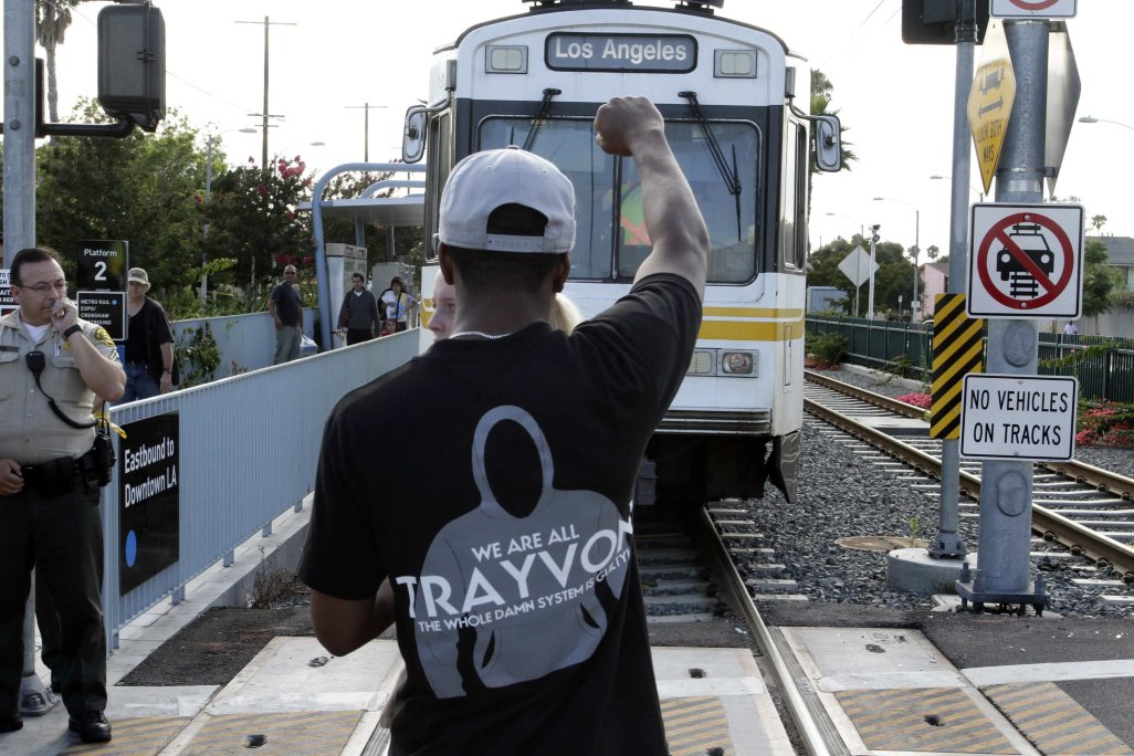 A demonstrator blocks a commuter train as they protest the acquittal of George Zimmerman in the Trayvon Martin trial, in Los Angeles