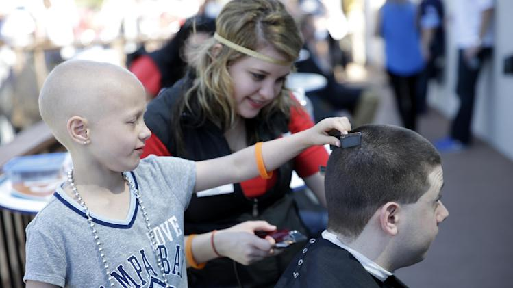 Tampa Bay Rays employee Peter Bendix gets his hair cut by cancer patient Ava Rabb, 5, of Tampa, Fla., before an exhibition baseball game against the Boston Red Sox in Port Charlotte, Fla., Sunday, March 16, 2014. The event was a fundraiser for the Pediatric Cancer Foundation. Behind is Jen Wheeler, of Sport Cuts. (AP Photo/Gerald Herbert)