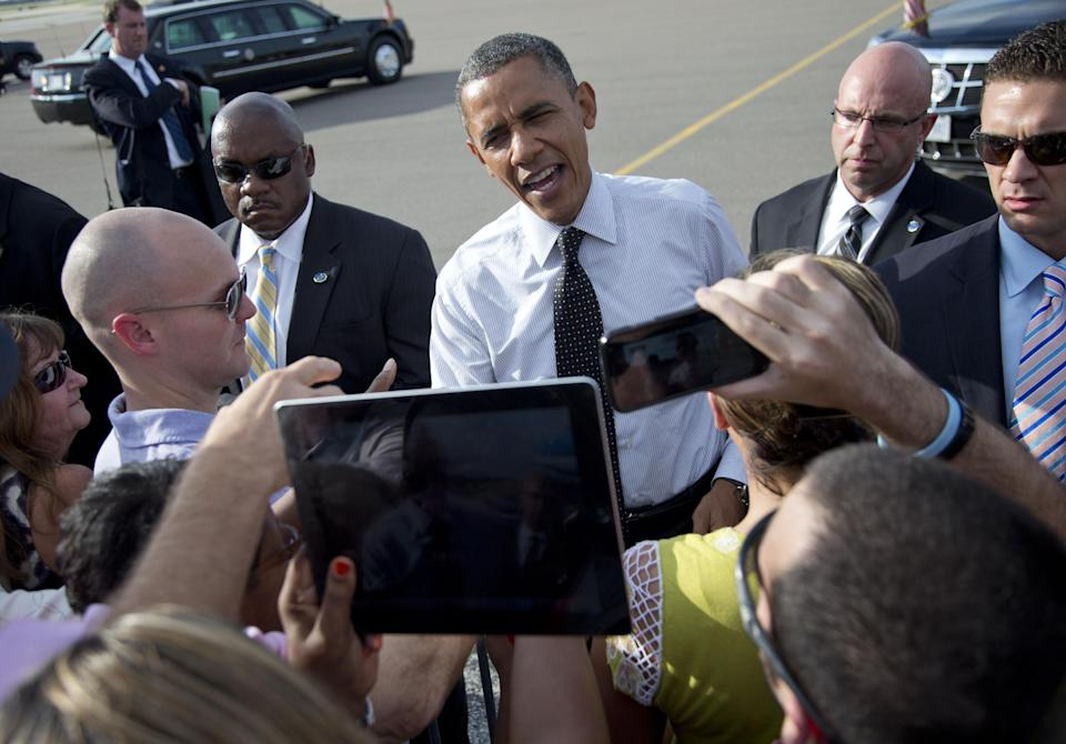 President Barack Obama greets people on the tarmac as he arrives at Tampa International Airport on Air Force One, Thursday, Sept. 20, 2012, in Tampa.  (AP Photo/Carolyn Kaster)
