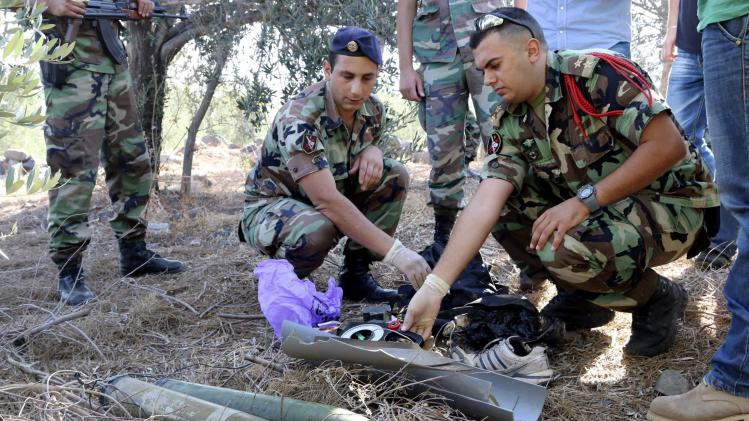 A Lebanese army personnel inspects the remains of a shell that was suspected of having been launched from Lebanon to Israel, near the village of El Mari in Southern Lebanon
