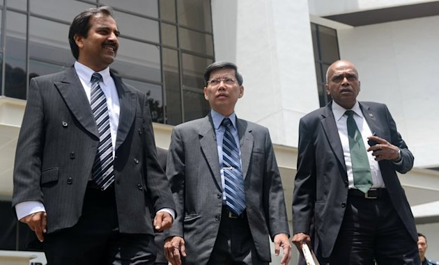 Peter Lim (C), Singapore's former civil defence chief, leaves court for a lunch break with his two lawyers, on February 18, 2013. Lim is on trial for allegedly demanding oral sex from a businesswoman bidding for government contracts. He denies the claim