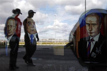 Police are reflected in the window of a shop displaying traditional nesting dolls with images of Russian President Putin, PM Medvedev and French President Hollande at the sea port in St. Petersburg
