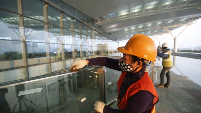 Workers clean glass panels as they put the finishing touches to the new terminal two wing at Noi Bai international airport in Hanoi