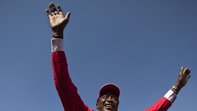 FILE - In this Saturday, March 2, 2013 file photo, Kenyan Presidential candidate Uhuru Kenyatta waves to the crowd from the sunroof of his vehicle as he arrives for the final election rally of The National Alliance party at Uhuru Park in Nairobi, Kenya. Kenya's Supreme Court on Saturday, March 30, 2013 upheld the election of Uhuru Kenyatta as the country's next president, in a verdict on a petition by candidate Raila Odinga appealing the election result, ending an election season that riveted the nation amid fears of a repeat of the 2007-08 postelection violence. (AP Photo/Ben Curtis, File)