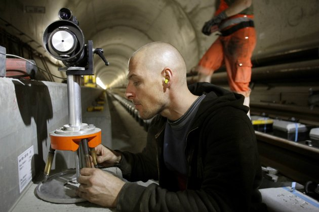 A worker adjusts a laser measuring gauge during the installation of the railway tracks in the NEAT Gotthard Base tunnel near Erstfeld