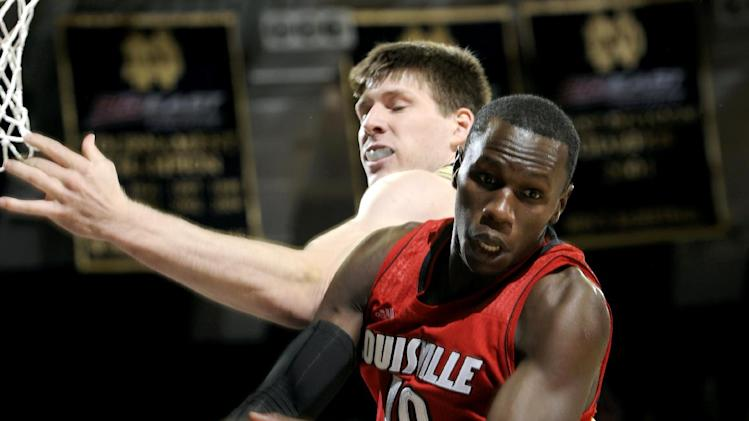 Louisville center Gorgui Dieng, right, grabs a rebound from Notre Dame forward Jack Cooley during the first half of an NCAA college basketball game, Saturday, Feb. 9, 2013, in South Bend, Ind. (AP Photo/Joe Raymond)