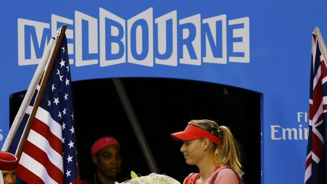 Williams of the U.S. watches as Sharapova of Russia receives flowers as she walks onto the court before the start of their women's singles final match at the Australian Open 2015 tennis tournament in Melbourne