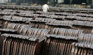 A worker inspects newly smelted copper anode sheets for delivery in Shanghai in 2005. Chinese private equity firm Cathay Fortune Corp has made an $850 million offer for Australia-listed Discovery Metals, Dow Jones Newswires reported Thursday, as China's copper demand continues to grow