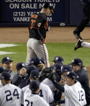 Baltimore Orioles' Matt Wieters, top, heads off the field as the New York Yankees celebrate their victory in game 5 of the American League division baseball series on Friday, Oct. 12, 2012, in New York. The Yankees won the game 3-1 and advanced to the AL championship. (AP Photo/Peter Morgan)