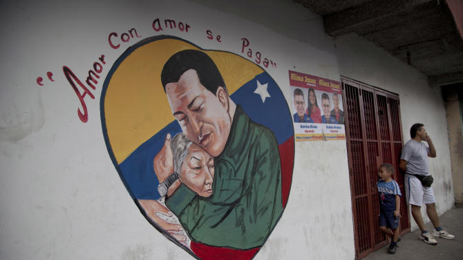 """A heart-shaped mural shows an image of Venezuela's President Hugo Chavez hugging a woman, in Caracas, Venezuela, Friday, Jan. 4, 2013. Chavez hasn't spoken publicly or been seen since his Dec. 11 operation in Cuba, and the latest report from his government Thursday night increased speculation that he is unlikely to attend his Jan. 10 inaugural ceremony. The message above the mural reads in Spanish; """"Love is repaid with love."""" (AP Photo/Ariana Cubillos)"""