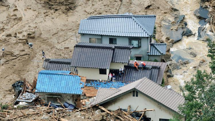 In this aerial photo, survivors and rescue workers sit on the roof of a damaged house after a massive landslide swept through residential areas in Hiroshima, western Japan, Wednesday, Aug. 20, 2014. Rain-sodden slopes collapsed in torrents of mud, rock and debris early Wednesday in the outskirts of Hiroshima, killing at least 36 people, police said. (AP Photo/Kyodo News) JAPAN OUT, MANDATORY CREDIT