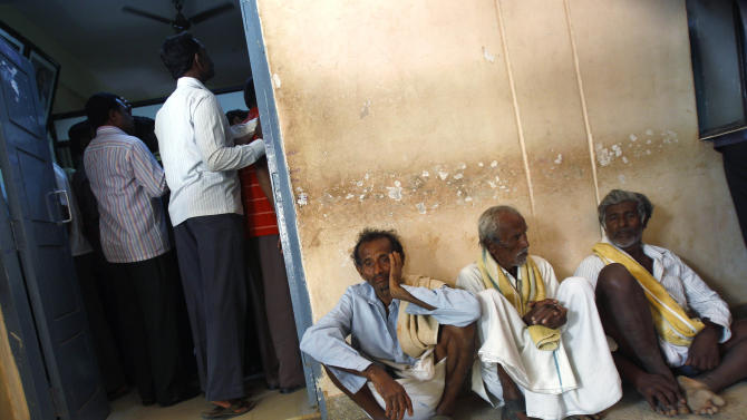 In this Dec. 10, 2012 photo, elderly villagers wait to get their land registered at the government registrar's office in Hoskote 30 kilometers (19 miles) from Bangalore in the southern Indian state of Karnataka. For years, Karnataka's land records were a quagmire of disputed, forged documents maintained by thousands of tyrannical bureaucrats who demanded bribes to do their jobs. In 2002, there were hopes that this was about to change. (AP Photo/Aijaz Rahi)