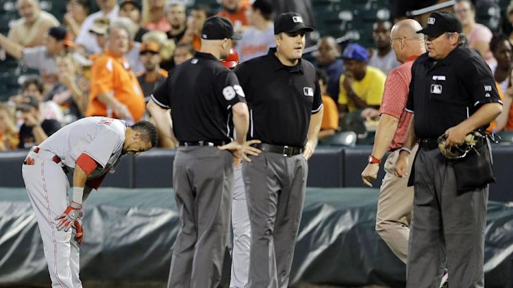 Cincinnati Reds' Billy Hamilton, left, pauses as umpires check on umpire Mike DiMuro, second from right, after the two collided in the first inning of an interleague baseball game, Tuesday, Sept. 2, 2014, in Baltimore. DiMuro left the field with a member of the Orioles athletic training staff after the play. (AP Photo/Patrick Semansky)