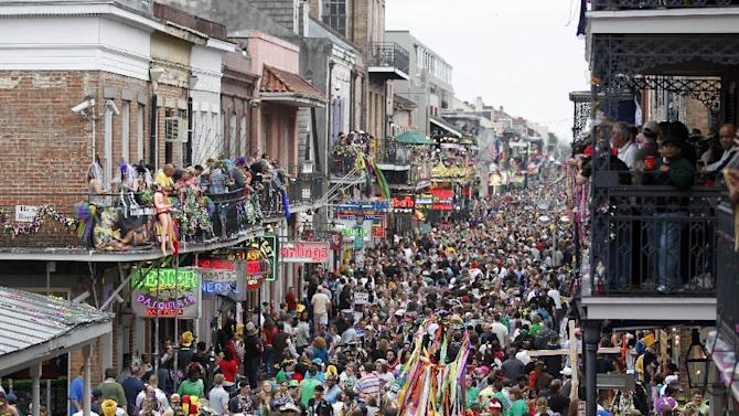 FILE - In this March 8, 2011 file photo, crowds throng Bourbon Street in the French Quarter on Mardi Gras day in New Orleans. New Orleans is perhaps best-known for hosting one of the biggest free parties in the world: Mardi Gras. The Carnival season includes parades with costumed riders, marching bands and decorated floats. (AP Photo/Gerald Herbert, file)