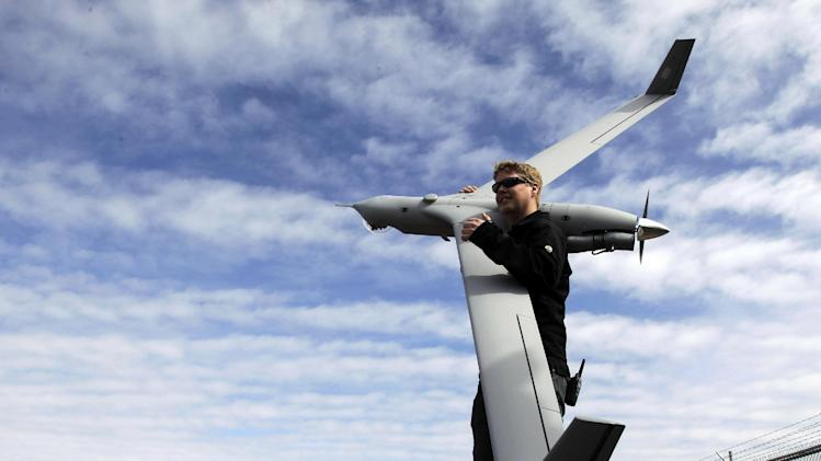 This photo taken March 26, 2013, shows flight test pilot Alex Gustafson carrying an InsituScanEagle unmanned aircraft in preparation for a flight in Arlington, Ore. It's a good bet that in the not-so-distant future aerial drones will be part of Americans' everyday lives, performing countless useful functions. A far cry from the killing machines whose missiles incinerate terrorists, these generally small unmanned aircraft will help farmers more precisely apply water and pesticides to crops, saving money and reducing environmental impacts. They'll help police departments to find missing people, reconstruct traffic accidents and act as lookouts for SWAT teams. They'll alert authorities to people stranded on rooftops by hurricanes, and monitor evacuation flows.  (AP Photo/Don Ryan)