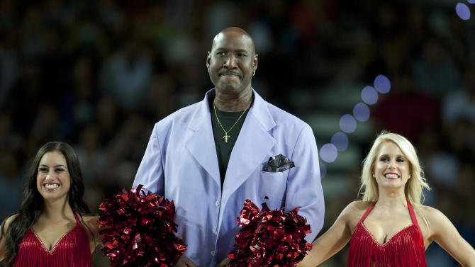 """FILE - In this Oct. 6, 2013, file photo, former Philadelphia's 76ers' Darryl Dawkins, center, receives a tribute before a match against Bilbao Basket, during an NBA Global basketball game in Bilbao, northern Spain. Darryl Dawkins, whose backboard-shattering dunks earned him the moniker """"Chocolate Thunder"""" and helped pave the way for breakaway rims, has died. He was 58. The Lehigh County, Pennsylvania coroner's office said Dawkins died Thursday morning, Aug. 27, 2015,  at a hospital. (AP Photo/Alvaro Barrientos, File)"""