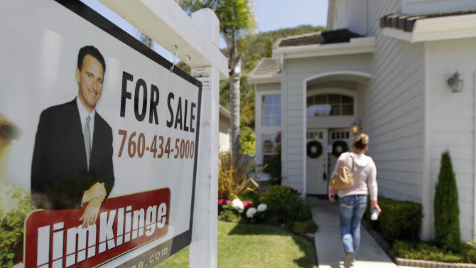 In this June 13, 2012, photo, a woman walks to an open house in San Diego. Mortgage buyer Freddie Mac said Thursday, June 14, 2012, that average rates on fixed mortgages rose this week, the first increase in seven weeks, but they remain near historic lows, boosting prospects for home sales this year. (AP Photo/Gregory Bull)