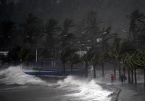 Residents walk past high waves brought about by strong …