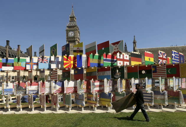 A worker carries a board while installing a display of international flags across the street from Big Ben Tuesday, July 24, 2012, in London. The city will host the 2012 London Olympics with opening ceremonies scheduled for Friday, July 27. (AP Photo/Charlie Riedel)