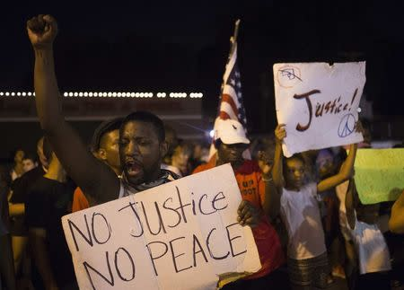 Demonstrators protest the killing of unarmed teen Michael Brown across the street from the Ferguson Police Department in Ferguson, Missouri