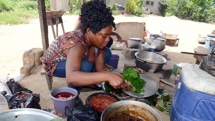 "A woman prepares food on April 8, 2014 at a ""maquis,"" a small restaurant, in Kobakro, outside Abidjan, which has stopped serving bushmeat since West Africa's Ebola outbreak"