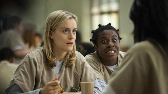 """FILE - This image released by Netflix shows Taylor Schilling, left, and Uzo Aduba in a scene from """"Orange Is the New Black."""" At the Emmy Awards being held Monday, Aug. 25, 2014, in Los Angeles, the prison-set dark comedy """"Orange Is the New Black"""" and political drama """"House of Cards"""" could become the first online series to claim top series awards. (AP Photo/Netflix, Paul Schiraldi, File)"""