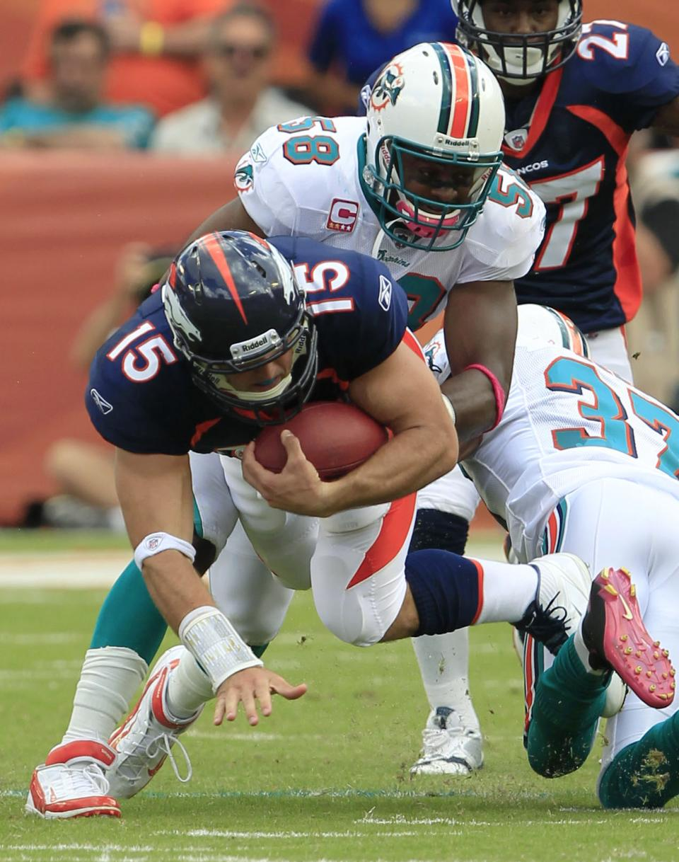 Denver Broncos quarterback Tim Tebow (15) is tackled by Miami Dolphins linebacker Karlos Dansby (58) and safety Yeremiah Bell (37) during the first half of an NFL football game Sunday, Oct. 23, 2011, in Miami. (AP Photo/Wilfredo Lee)