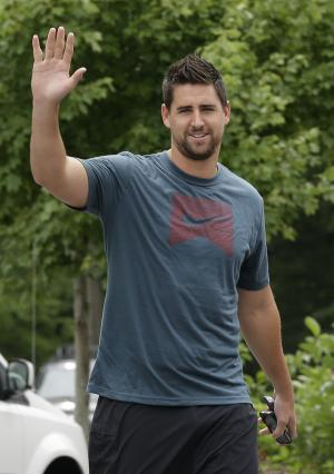 Baltimore Ravens tight end Dennis Pitta waves to reporters as he reports to the team's practice facility in Owings Mills, Md., Wednesday, July 24, 2013, for NFL football training camp. (AP Photo/Patrick Semansky)