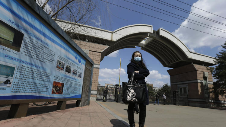 A woman with a mask stands near the entrance to the Northeast Yucai school where one of victims of the Boston Marathon explosions, Lu Lingzi, studied during her high school education in Shenyang, north eastern China's Liaoning province, Thursday, April 18, 2013. Lu, who was killed in the Boston Marathon blasts, grew up in an intellectual family in a provincial capital with gritty, industrial roots, and graduated from a highly competitive high school that routinely sends students abroad. (AP Photo/Ng Han Guan)