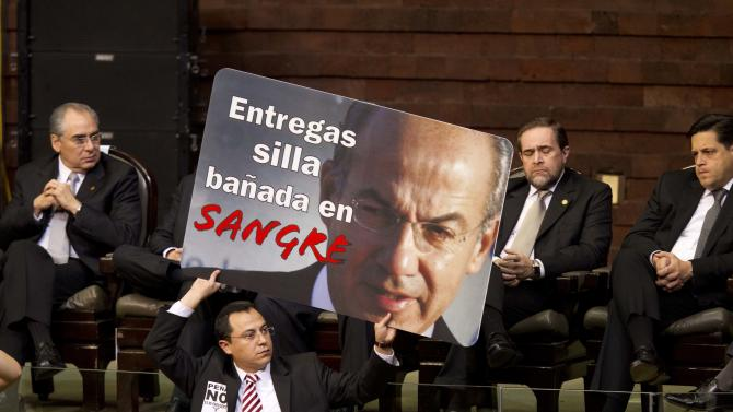 "A member of Mexico's National Congress holds a poster with an image of outgoing President Felipe Calderon that reads in Spanish: ""You are giving a chair bathed in blood,"" prior to the inauguration ceremony of incoming President Enrique Pena Nieto in Mexico City, Saturday, Dec. 1, 2012.  Pena Nieto took the oath of office as Mexico's new president on Saturday, bringing the old ruling party back to power after a 12-year hiatus amid protests inside and outside the congressional chamber where he swore to protect the constitution and laws of the land. (AP Photo/Alexandre Meneghini)"