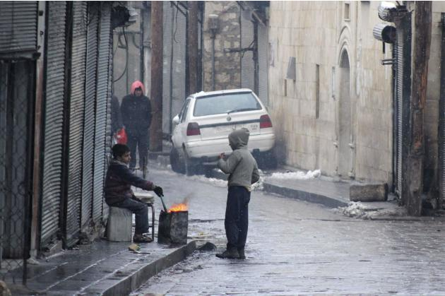 Children warm themselves around a fire as it snows, along a street in the city of Aleppo